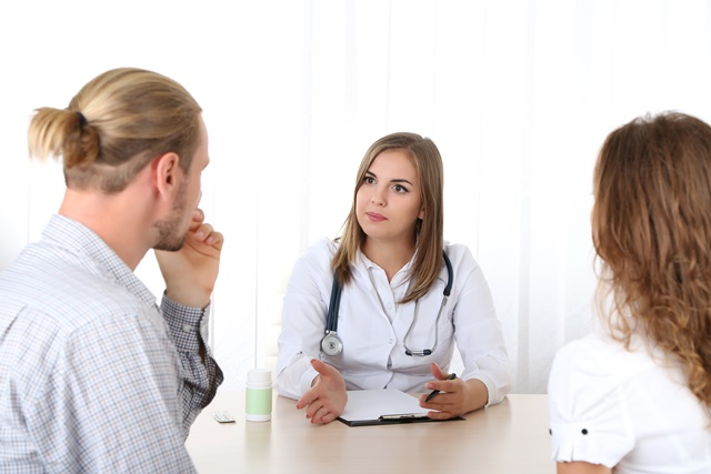 Doctor and young couple patients at office